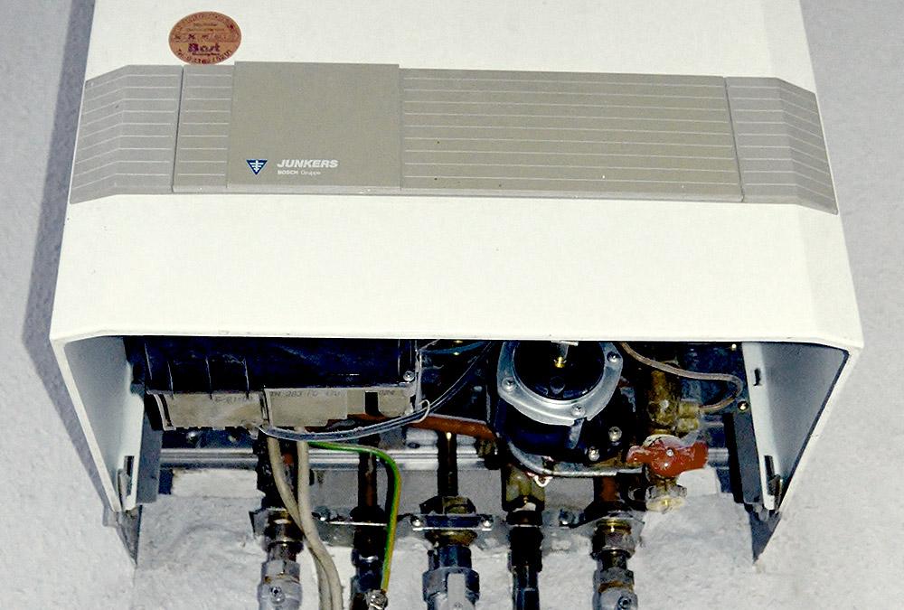 Die Unterseite einer Therme. Elektrische Bauteile und die Zuleitung für Gas und Wasser sind gut zu sehen.